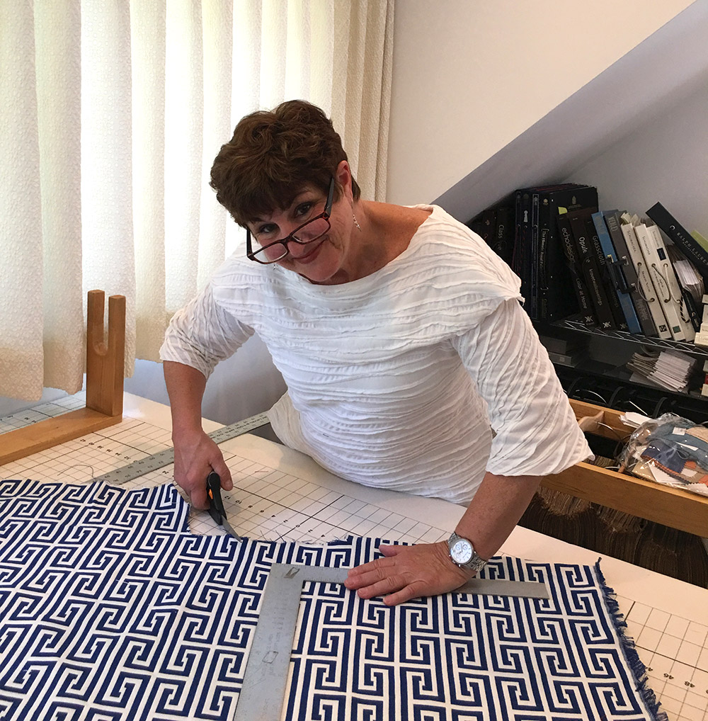 Debbie Farrand of Dressing Rooms Interior Design working on a custom fabric piece for a client.